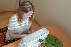 белошвейка сидя на таблице со швейной машиной, стоковые фотографии rf