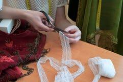 Белошвейка сидя на таблице, швейной машине и режа шнурок с ножницами в шить студии стоковое изображение