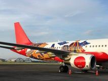 Бело-красный самолет на взлетно-посадочной дорожке стоковая фотография