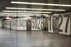Бело-серая комната Освещение в длинном коридоре Светлые стены, зеркало с номерами, и пол блеск Справочная информация стоковое фото