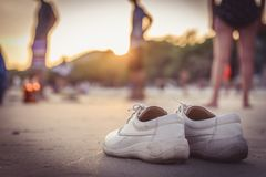 Белые ботинки на пляже с винтажным стилем стоковая фотография