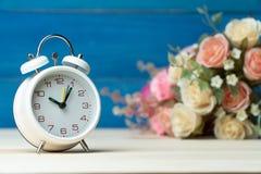 Белые будильник и цветки пинк и красная роза на деревянном столе и голубая предпосылка с космосом экземпляра для добавляют текст  стоковые изображения