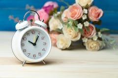 Белые будильник и цветки пинк и красная роза на деревянном столе и голубая предпосылка с космосом экземпляра для добавляют текст  стоковое изображение rf