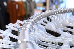 Белые вешалки на круглом шкафе установили вид хаотически в магазине, DOF стоковое изображение