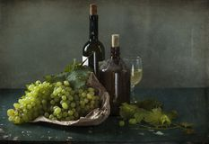 Белые виноградины, бутылки вина и бокал вина Стоковое фото RF