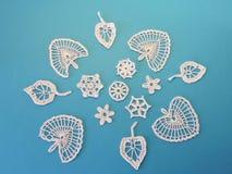 Белые вязать крючком крючком листья и цветки на голубой предпосылке Стоковое Фото