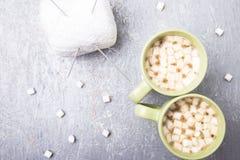 Белые вязать шарик и иглы в 2 чашках кофе с зефиром на серой предпосылке Взгляд сверху скопируйте космос Вязать пряжа Стоковая Фотография