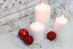 Белые горящие свечи, красные безделушки рождества Стоковые Фото