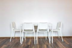 Белые деревянные стулья с таблицей на фоне белой стены в интерьере стоковые изображения