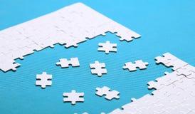 Белые детали головоломки на зеленой предпосылке Головоломка puz стоковые фотографии rf