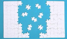 Белые детали головоломки на зеленой предпосылке Головоломка puz стоковые изображения