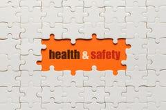Белые детали головоломки на оранжевых предпосылке и здоровье и безопасности слова стоковые фотографии rf