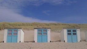 Белые и голубые кабины на пляже стоковая фотография