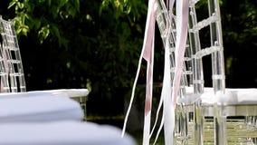Белые и розовые ленты порхая на стульях Свадебная церемония Прозрачные стулья сток-видео