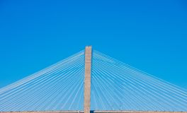 Белые кабели на висячем мосте против голубых небес стоковое изображение