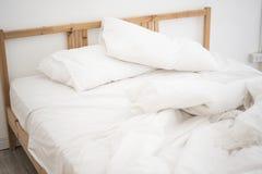 Белые листы и подушка постельных принадлежностей в белой спальне грязно стоковые изображения