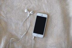 Белые наушники и белый телефон flatlay стоковые фото