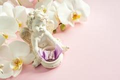 Белые обручальные кольца скульптуры ангела орхидеи на розовой предпосылке Стоковое фото RF