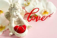 Белые обручальные кольца скульптуры ангела орхидеи на розовой предпосылке Стоковые Изображения