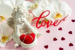 Белые обручальные кольца скульптуры ангела орхидеи на розовой предпосылке Стоковое Изображение RF