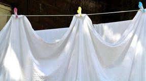 Белые одежды вися вне для того чтобы высушить Стоковые Изображения