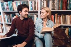 Белые парень и девушка около книжных полок в библиотеке Студенты книги чтения Стоковые Фотографии RF