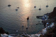 Белые парусные судна в и вне порт Oia для красивого взгляда захода солнца с предпосылкой отражения света океана моря Стоковые Изображения