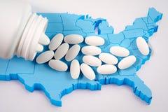 Белые пилюльки рецепта разливая от бутылки медицины над картой Америки Стоковая Фотография RF