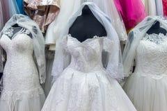Белые платья на манекенах в салоне свадьбы стоковые фотографии rf