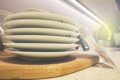 белые плиты и дисплей dinnerware на полке с светлым влиянием пирофакела Стоковое Фото