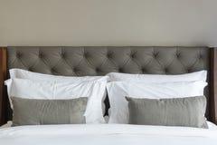 Белые подушки на кровати в современной комнате Стоковая Фотография