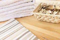 Белые полотенца и корзина с пряными сухими заводами на светлой деревянной предпосылке, покрытой с striped тканью стоковая фотография rf