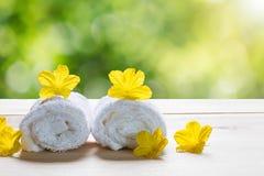 Белые полотенца с желтыми цветками на деревянном поле на запачканной зеленой предпосылке bokeh Стоковые Фото