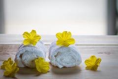 Белые полотенца с желтыми цветками на деревянном столе на запачканной предпосылке Стоковое Фото