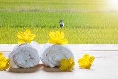 Белые полотенца с желтыми цветками на деревянном столе на запачканной зеленой предпосылке луга Стоковое Изображение RF