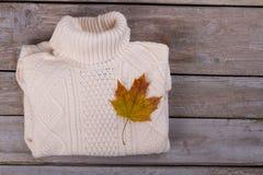 Белые пуловер и кленовый лист Стоковые Изображения