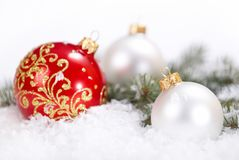 Белые рождества красивые и красные шарики с ветвью и снегом ели на белой предпосылке Стоковая Фотография RF