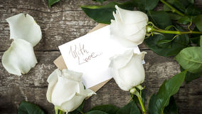 Белые розы с изолированным письмом на таблице Стоковое Изображение