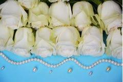Белые розы с шариками жемчуга на голубой предпосылке Стоковое Изображение RF