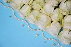 Белые розы с шариками жемчуга на голубой предпосылке Стоковое Фото