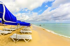 Белые салоны фаэтона и голубая стойка зонтиков на пляже в th Стоковое Изображение