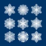Белые силуэты снежинок изолированные на темно-синей предпосылке, v бесплатная иллюстрация