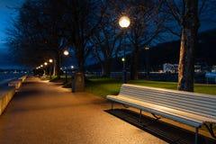 Белые скамейки в парке в парке в Bregenz после захода солнца стоковые фотографии rf
