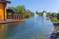 Белые сочные фонтаны распыляют воду на озере около деревянных домов с террасой Стоковые Изображения RF