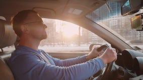 Белые спады водителя позволяя другим автомобилям пройти мимо Улыбки и кивки человека к музыке Небо с заходом солнца Backlight сток-видео