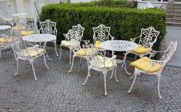 Белые стулья и таблицы на кафе на улице стоковое фото rf