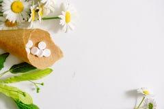 Белые таблетки в klubke kraft, лекарственные растения зеленых лист, гомеопатическая медицина Лист цветут и приносить липы, flo ст Стоковое фото RF