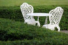 Белые таблица и стул в саде Стоковые Изображения RF