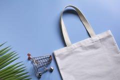 Белые ткань холста сумки tote и тележка прерывать Модель-макет мешка ткани ходя по магазинам с космосом экземпляра стоковое изображение rf