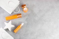 Белые хозяйственные сумки и оранжевые косметические образцы на серой конкретной предпосылке стоковая фотография